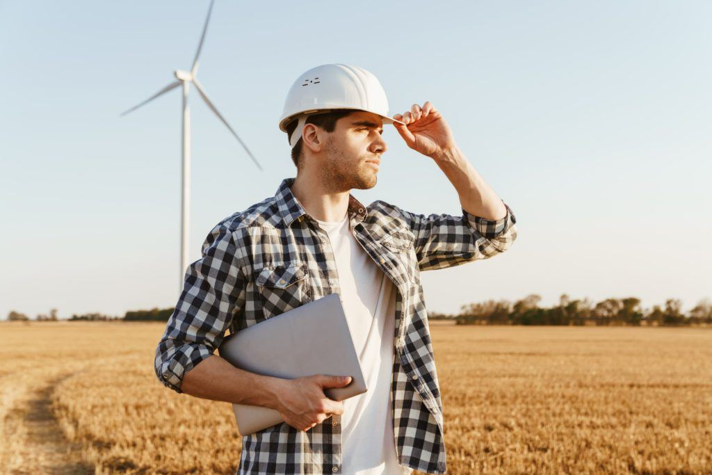 An electrical engineer standing on a field